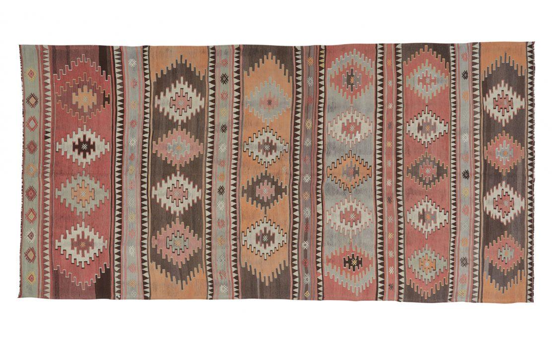 Stribet stor kelim tæppe med brændte farver i okker, rød, brun og sand, med mint og mørke detaljer. Tæpper sælges i København