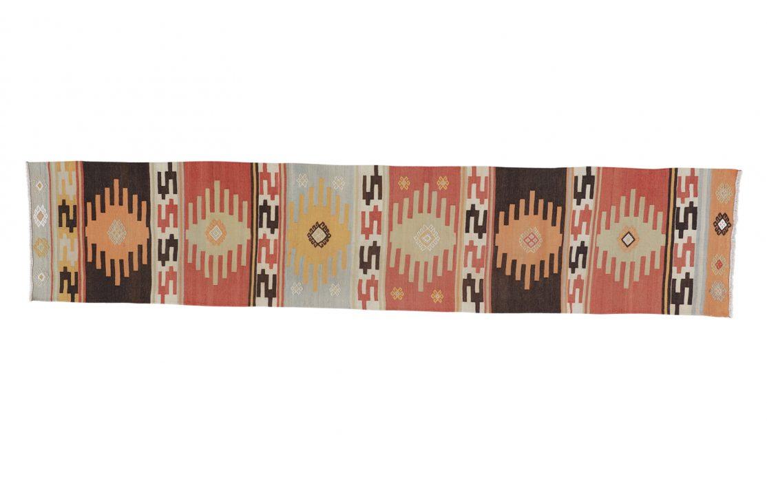 Stribet tyrkisk kelim tæppe løber i brændte farver af rød, okker, brun og gylden, med mint detalje. Tæpper sælges i København