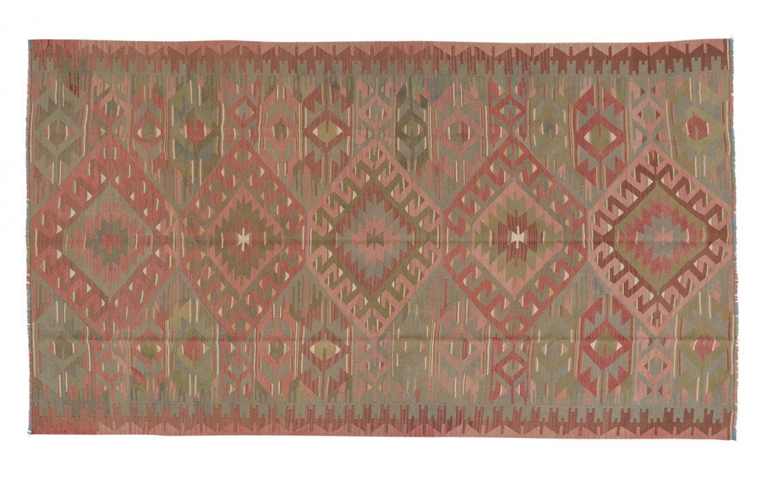 Stor tyrkisk kelim tæppe i rosa, bordeaux og støvet grøn med bund af varm grå. Tæpper sælges i København.