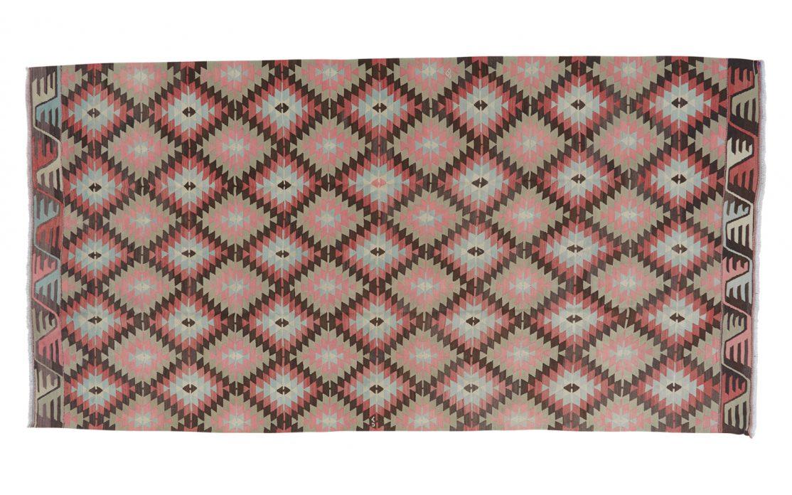 Stor grafisk tyrkisk kelim tæppe i diamantmønster med farver af rosa, messing og sart turkis. Tæpper sælges i København