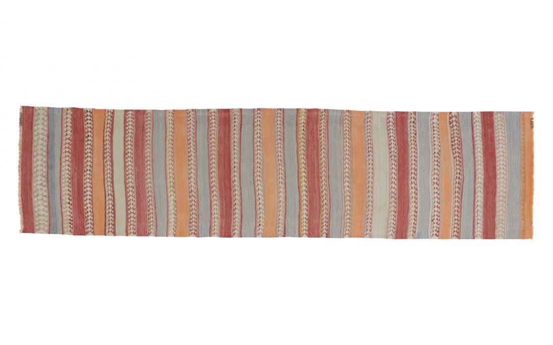 Stribet tyrkisk kelim tæppe løber i støvet orange, gråblå, støvet rød og sandfarver med detaljer i vævningen. Tæpper sælges i København