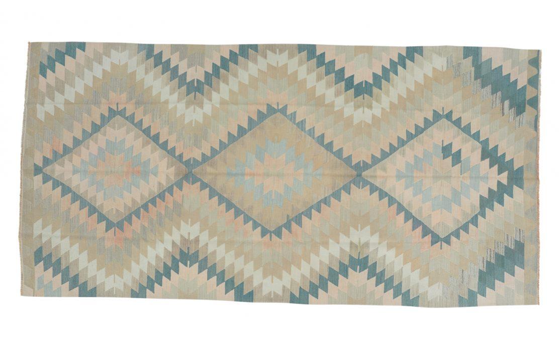 Tyrkisk stor kelim tæppe i afdæmpede farver. Støvet turkis, sand, sart fersken og gyldne farver med stjernemønster. Tæpper sælges i København