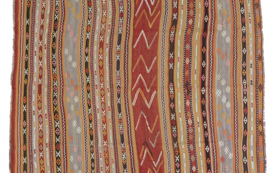 Tyrkisk stribet kelim tæppe i gyldne rustrøde farver med broderede detaljer. Tæpper sælges i København