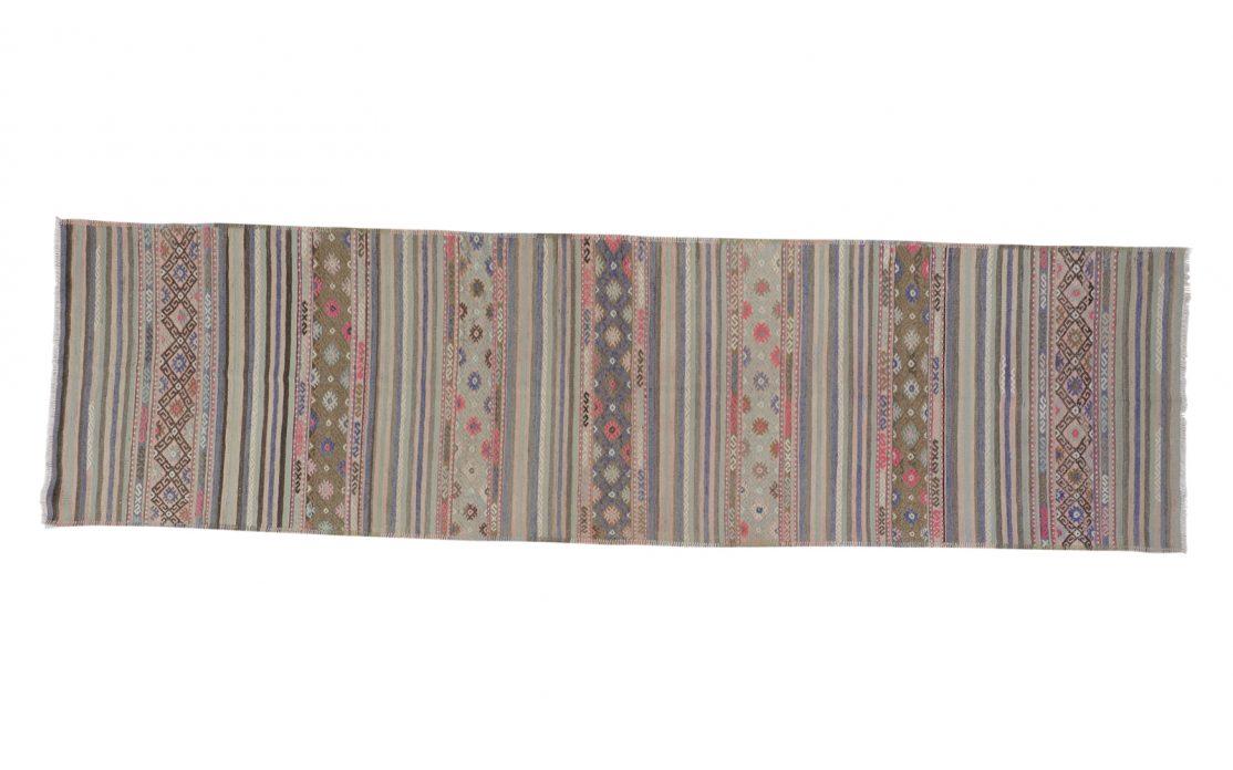 Tyrkisk stribet kelim tæppe løber i grønne, blå og gyldne farver med pink detaljer. Tæpper sælges i København