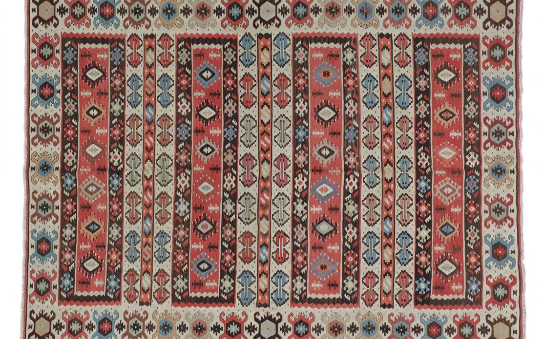 Tyrkisk kelim tæppe på bund af beige med støvet rød og blå detaljer. Tæpper sælges i København