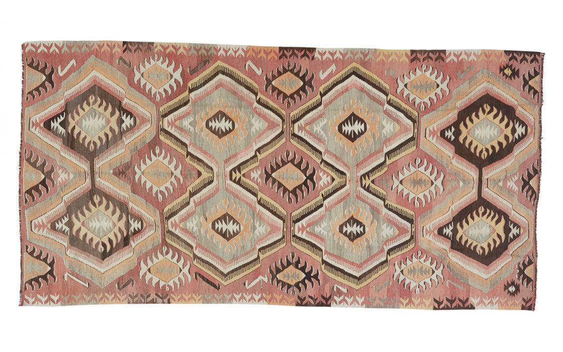 Stor grafisk tyrkisk kelim tæppe i rosa nuancer med detaljer af brun, mint, gylden og sand. Tæpper sælges i København