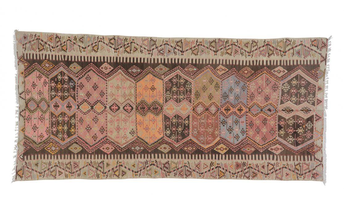Stor tyrkisk kelim tæppe i sarte brændte farver på en bund af rosa og beige. Tæpper sælges i København