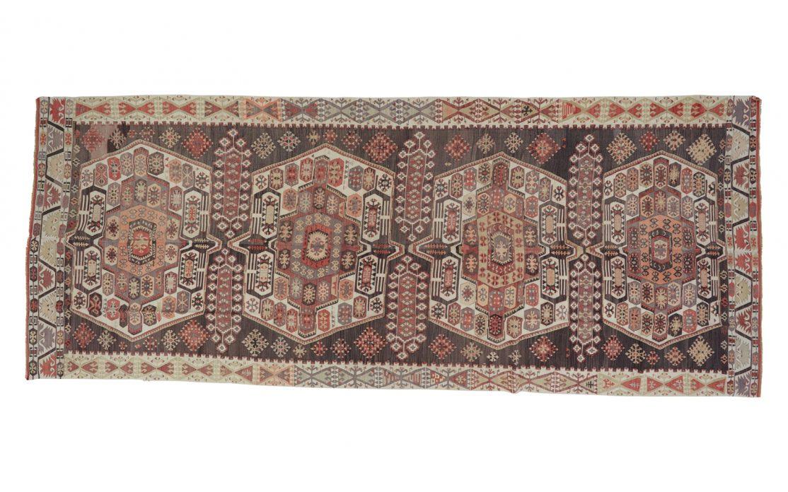 Stor tyrkisk kelim i varme farver af bordeaux, brun, grå med røde detaljer. Tæpper sælges i København