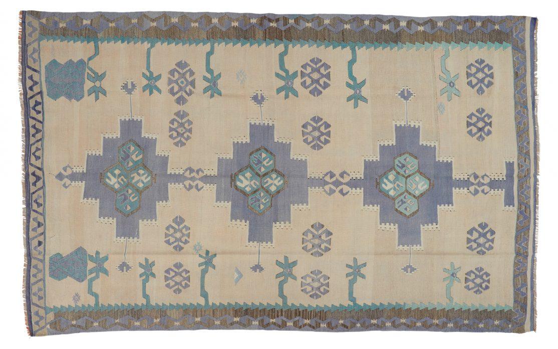 Lyst tyrkisk kelim tæppe i sand med detaljer af blå, mint, lilla og grå. Tæpper sælges i København