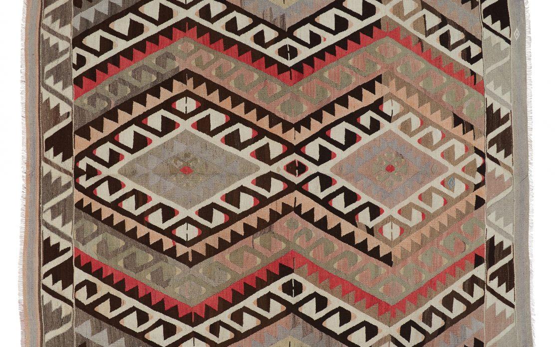 Grafisk tyrkisk kelim tæppe i nuancer af beige, brun og sand med detaljer af gylden og rød. Tæpper sælges i København