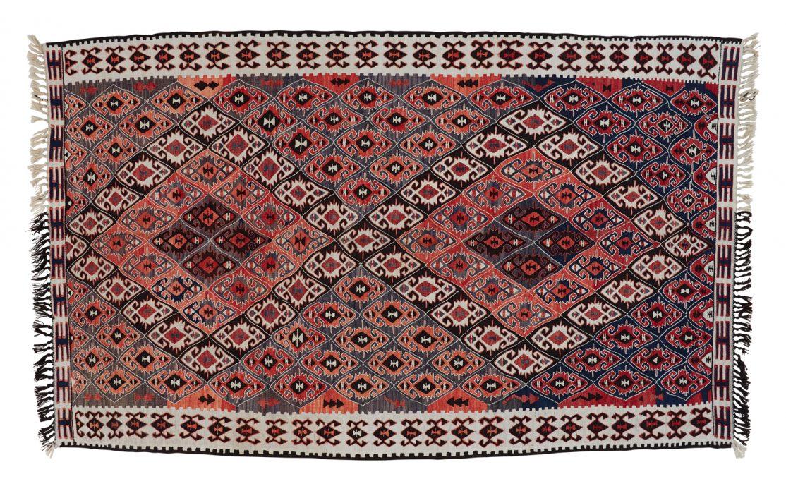 Tyrkisk kelim tæppe i nuancer af bordeaux og blå med grå detaljer og frynser. Tæpper sælges i København