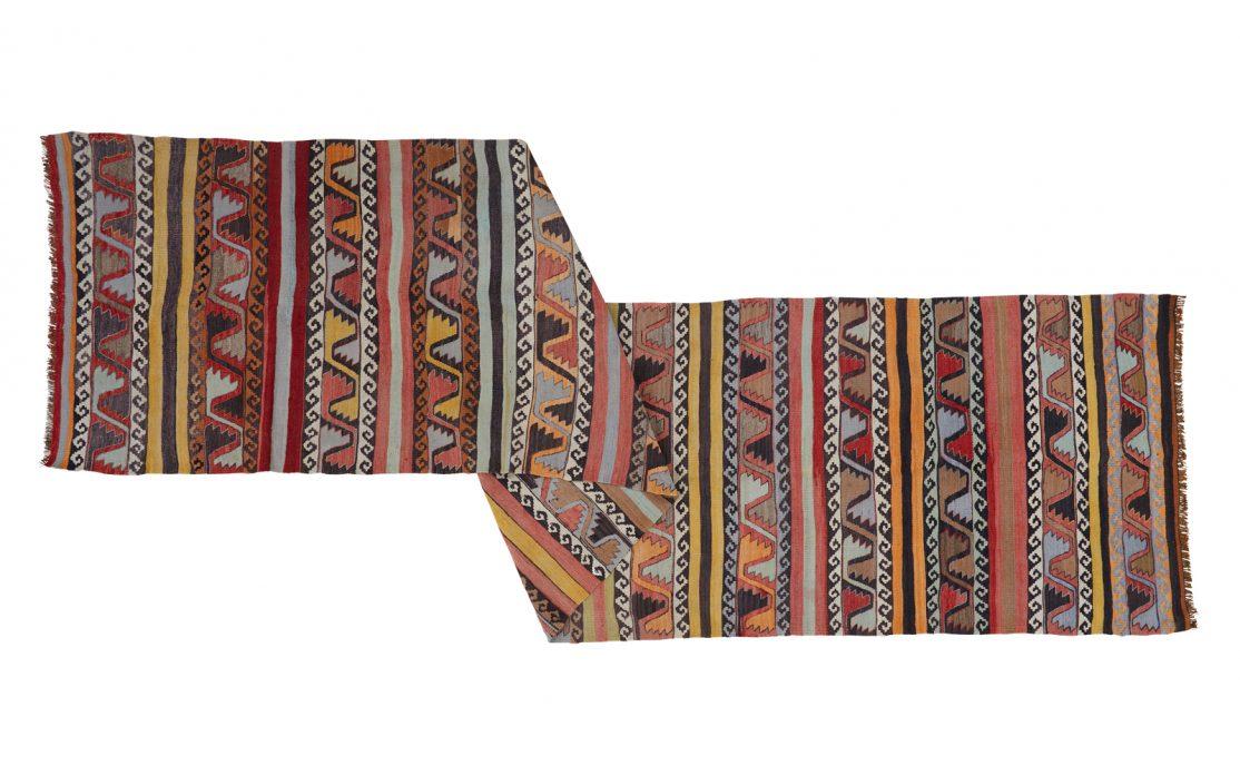 Stribet tyrkisk kelim tæppe løber i varme farver i bordeaux, orange, brun med detaljer i blå. Tæpper sælges i København