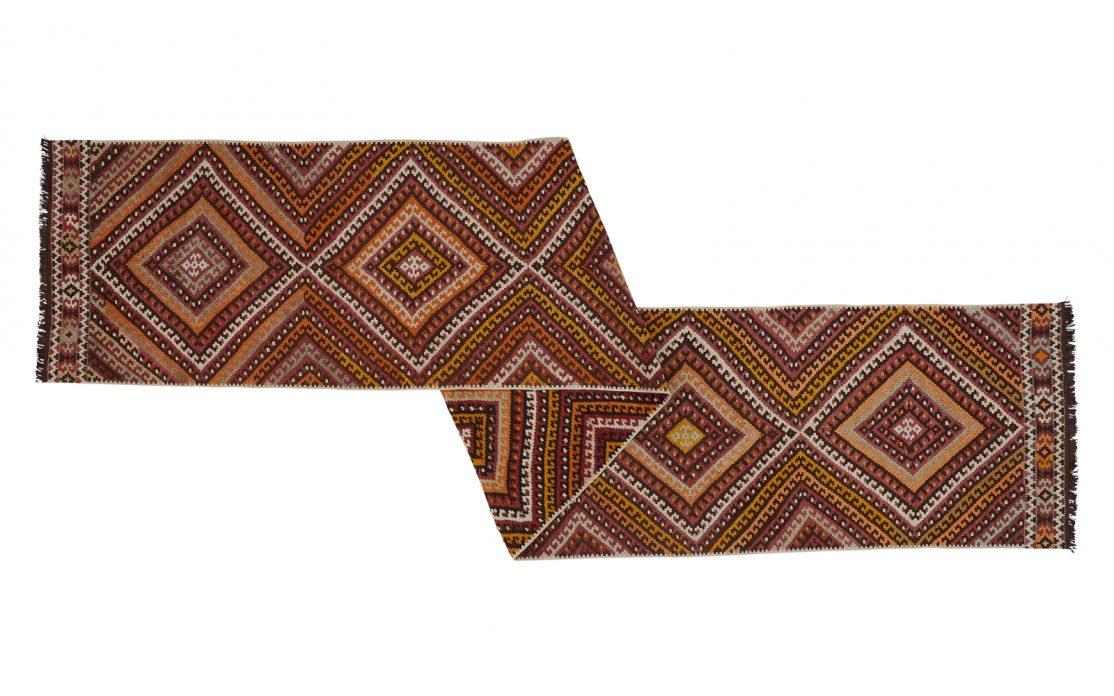 Lang tyrkisk kelim tæppe løber i brændte farver af brun, orange, okker, oliven og lilla. Tæpper sælges i København