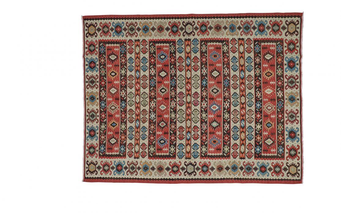 Tyrkisk kelim tæppe i rød nuance med detaljer af sand, blå og sort. Tæpper sælges i København