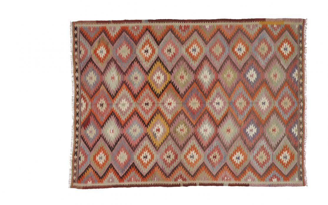 Tyrkisk kelim tæppe i diamantmønster med farver af rød, bordeaux og farverige detaljer. Tæpper sælges i København