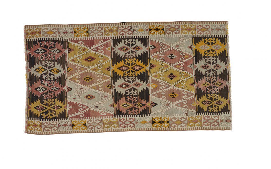 Tyrkisk kelim tæppe i farver af rosa, beige, gul og sort. Tæpper sælges i København