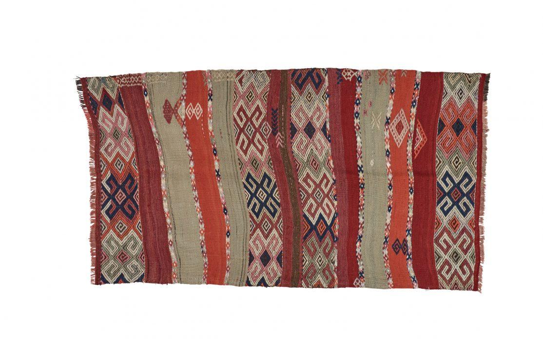 Tyrkisk kelim tæppe i røde, bordeaux, rosa og grå farver. Tæpper sælges i København