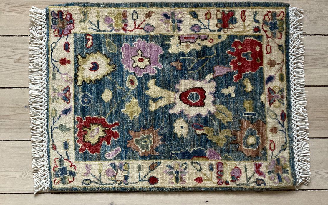 Håndknyttet måtte i multi farve med blomster mønster. Måtter sælges i København